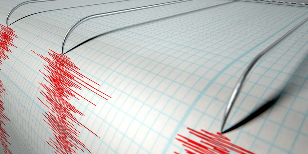 A closeup of a seismograph machine needle drawing a red line on graph paper depicting seismic and eartquake activity on an isolated white background