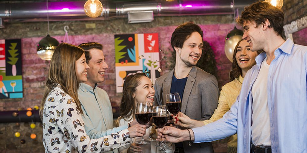 group-smiling-male-female-friends-toasting-wine-club-night